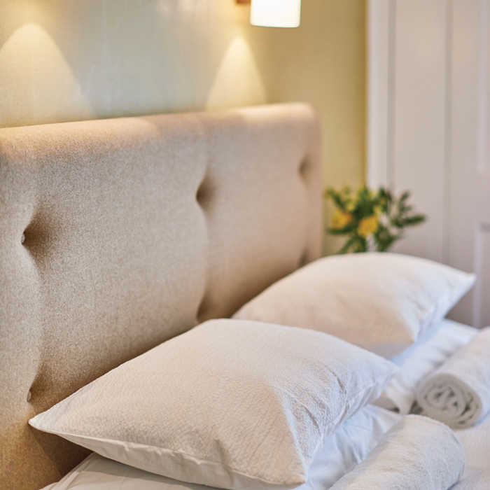 The padded headrest of the double bed in the superior room