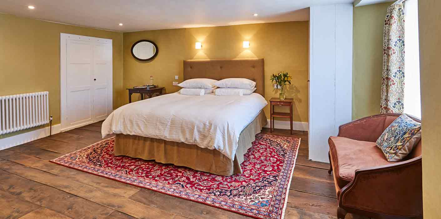 Open shot of king size bed and warm decor at Rook Lane House